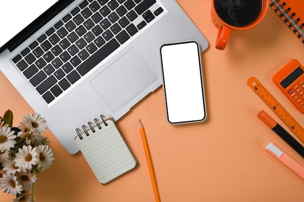 Bespotten van mobiele telefoon, computer laptop en rekenmachine op beige achtergrond.