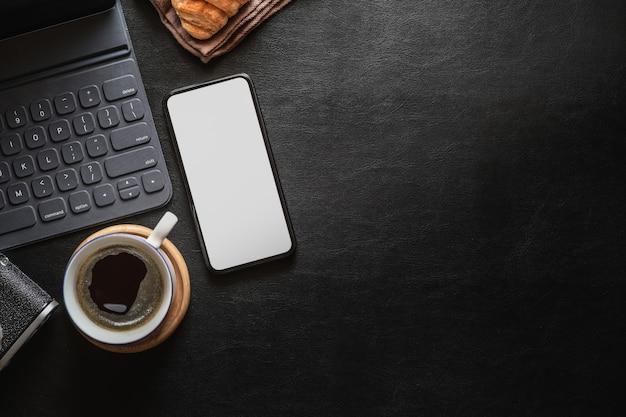 Bespotten van mobiele telefoon op donker bureau van het thuiskantoor en exemplaarruimte