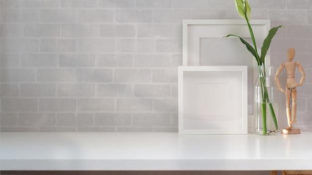 Bespotten van poster of fotolijst en benodigdheden op minimalistische werkplek op zolder