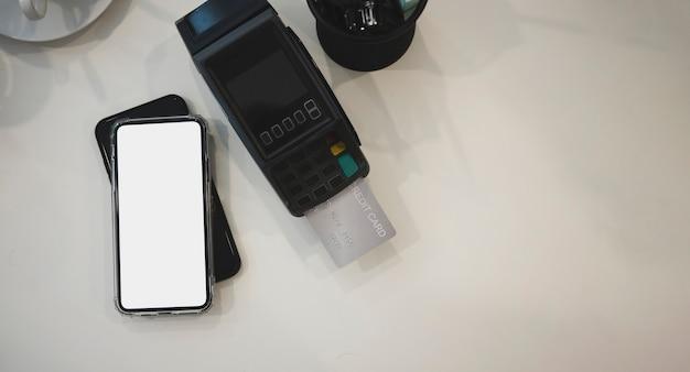 Bespotten van slimme telefoon en creditcardmachine op wit bureau.