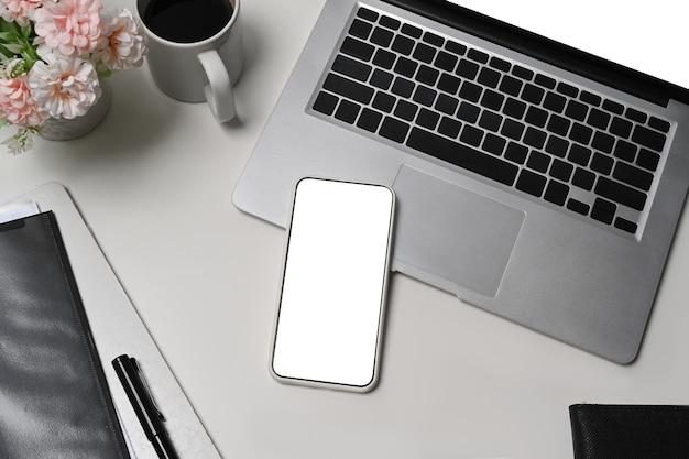 Bespotten van slimme telefoon, laptopcomputer en koffiekopje op wit bureau.
