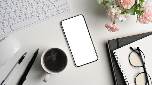 Bespotten van slimme telefoon met leeg scherm, koffiekopje en kantoorbenodigdheden op wit bureau.