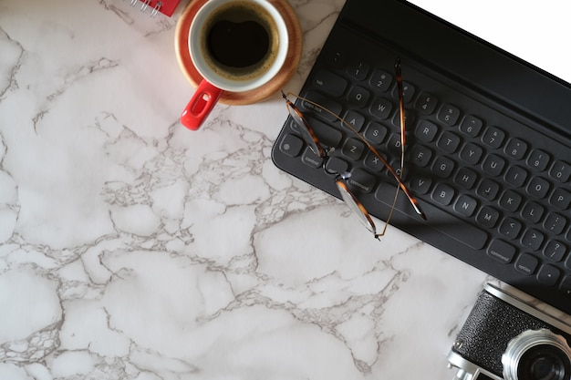 Bespotten van tablet met slimme toetsenbord, vintage camera op marmeren werkplek