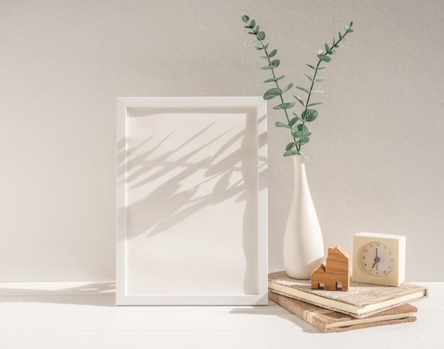 Bespotten van wit houten posterframe eucalyptus gedroogd blad in vaas klokboeken huismodel op tafel