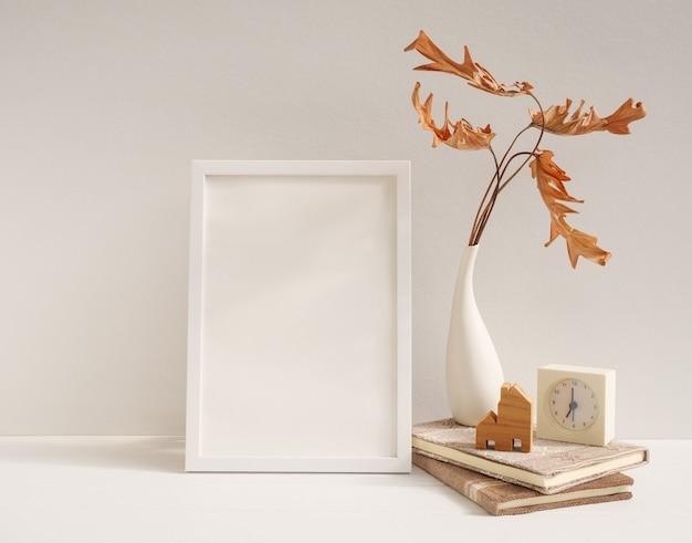 Bespotten van wit houten posterframe, philodendron gedroogd blad in vaas klokboeken huismodel op beige tafel