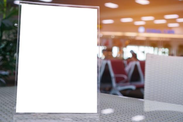 Bespotten van wit label op tafel voor blanco menuframe in restaurant voor boekjes met vellen papier, standaard voor acryltentkaart gebruikt voor menubalk, vervaging van groene achtergrondinvoeging voor tekst van klant.
