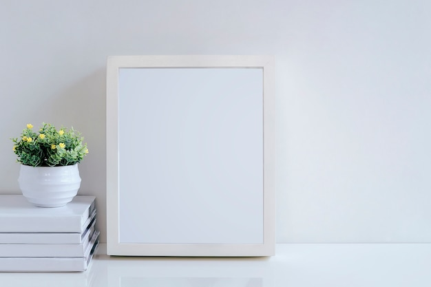 Bespotten van witte houten frame, boeken en kamerplant op witte tafel