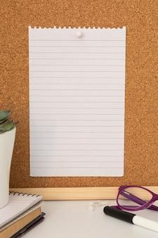 Bespotten werkruimte met leeg papier met kopie ruimte op cork board.