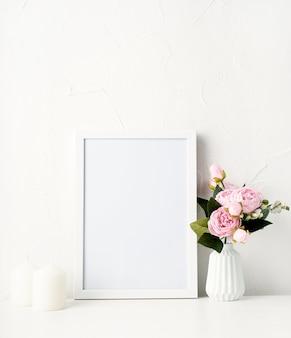 Bespotten wit frame aan de muur met pioenrozen en witte kaarsen
