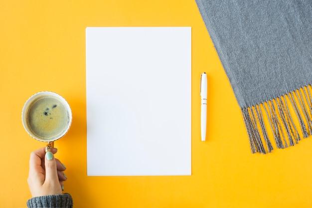 Bespotten - wit vel papier naast een kopje koffie in de vrouwelijke hand