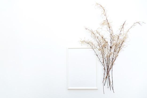 Bespotten witte fotolijst plat leggen met pampagras op een witte muur