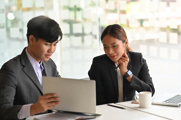 Bespreek zaken met twee mensen het bedrijfs raadplegen op laptop computer.