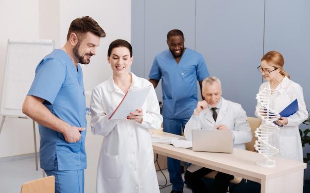 Bespreken van belangrijke kwesties. positieve vriendelijke bekwame artsen studeren en genieten van de lezing in de medische universiteit terwijl ze hun kwalificaties verbeteren en meningen delen
