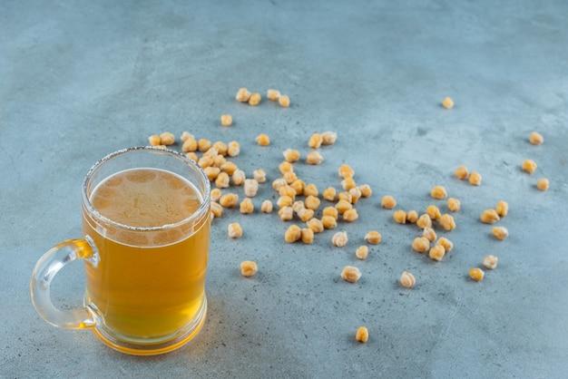 Besprenkeld kikkererwten en glas bier, op de marmeren tafel.