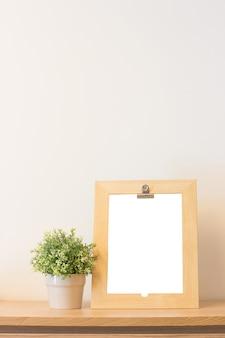 Bespul houten frame en plant op boekenplank of bureau.