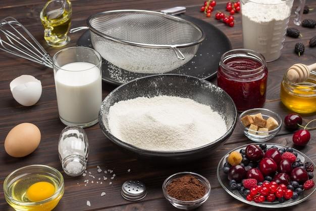 Bessen, gezeefd meel in zwarte plaat, cacaopoeder. maatbeker met bloem, glas melk, gebroken ei en zout, metalen garde op tafel.