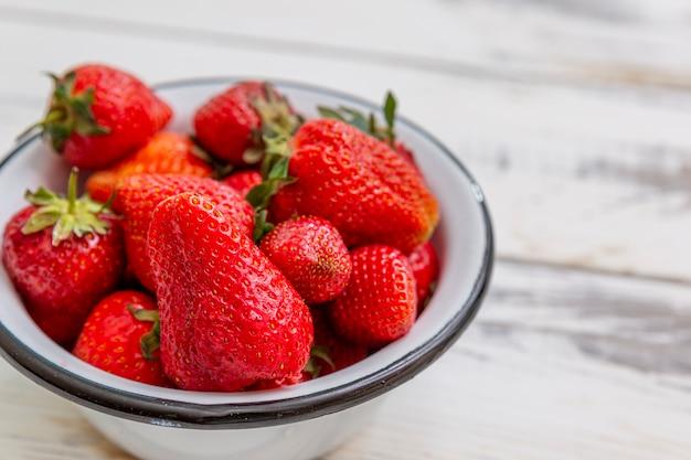 Bessen van rijpe rode aardbeien in een kom op een lichte houten achtergrond. seizoensgebonden vitamines. detailopname. bovenaanzicht.