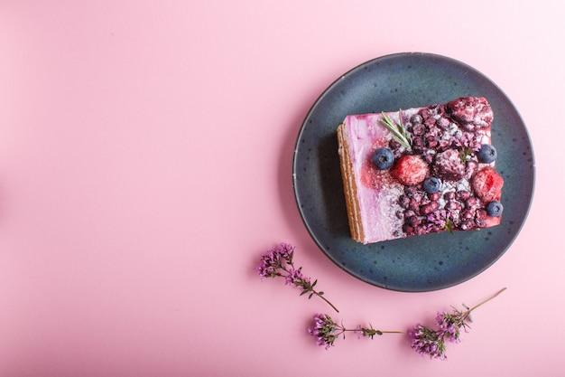 Bessencake met melkroom en bosbessenjam op blauwe ceramische plaat. bovenaanzicht.