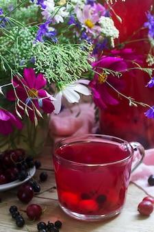 Bessencompote in een glaskop, bessen en een boeket van wilde bloemen op een deoanean achtergrond. rustieke stijl.