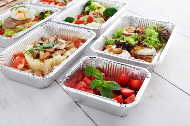 Bessendessert en andere gerechten voor bezorging in het restaurant. zoete aardbeiensalade in foliedoos bij wit hout. gezond eten om mee te nemen
