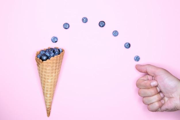 Bessenijs. blueberry in een hoorn. op een achtergrond voor een inscriptie. hand en ijs. bovenaanzicht vitamines concept. plaats voor een inscriptie. bes liefde concept.