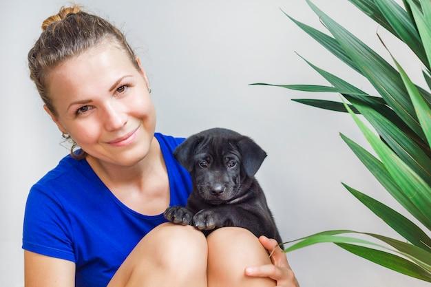 Best leuk meisje, kleine kleine schattige zwarte puppy op handen houden. het jonge mooie vrouw glimlachen, die met hond spelen, die pret met haar huisdier hebben. vriendschap tussen mens en hond. huisdieren en dieren concept