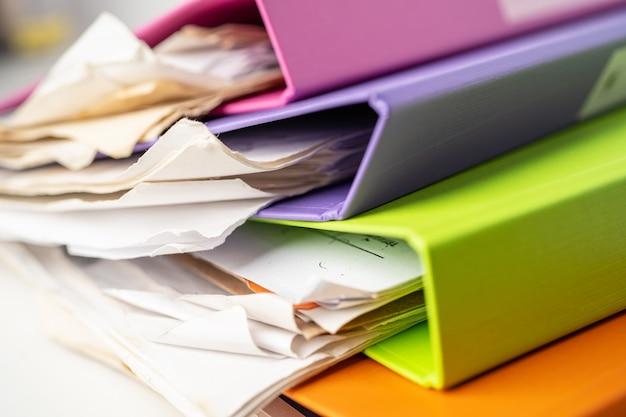 Bestandsmap binder stapel van meerdere kleuren op tafel in kantoor.