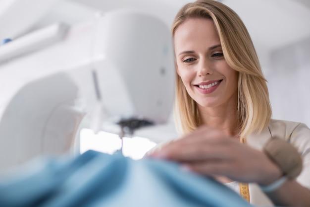 Beste baan. lage hoek van gelukkige vrouwelijke kleermaker met behulp van naaimachine en naar beneden te staren