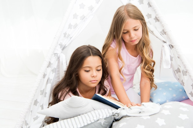 Beste boeken voor kinderen. kinderen lezen boek in bed. lezen voor het slapengaan kan helpen om 's nachts beter te slapen. verhalen die elk kind zou moeten lezen. familie traditie. meisjes beste vrienden lezen sprookje voor het slapengaan.