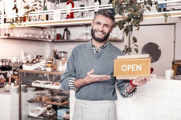 Beste café. vrolijke aardige man die duimen omhoog gebaar toont terwijl hij je zijn café aanbeveelt