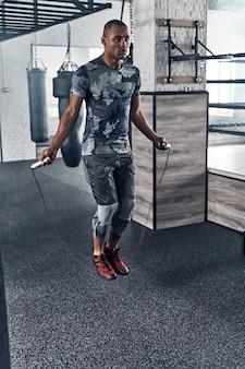 Beste cardio ooit. volledige lengte van jonge afrikaanse man in sportkleding springtouw