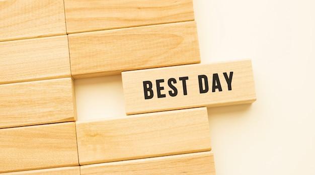 Beste dag tekst op een strook hout liggend op een witte tafel.