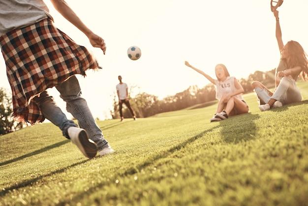 Beste fans! twee jonge vrouwen die op het gras zitten en gebaren maken terwijl hun mannelijke vrienden buiten voetballen
