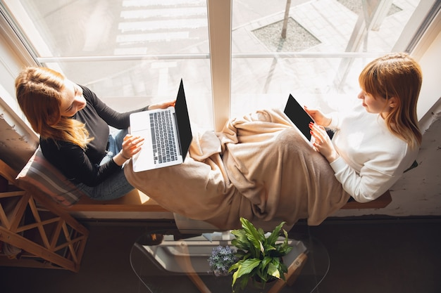 Beste herinneringen. jonge vrienden, vrouwen die gadgets gebruiken om films te kijken, foto's, online cursussen, selfies maken of vloggen. twee blanke vrouwelijke modellen thuis in de buurt van raam met behulp van laptop, tablet, smartphone.