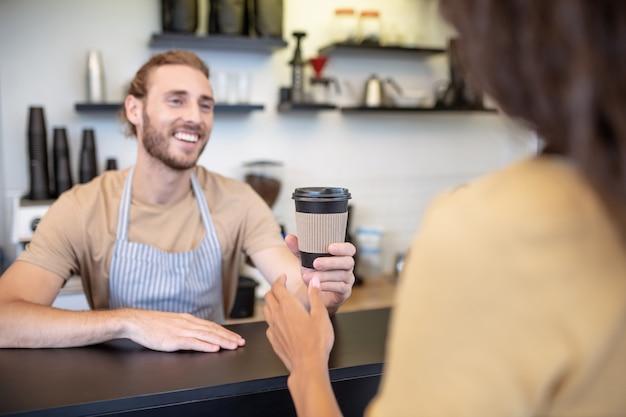 Beste koffie. jonge volwassen lachende man in schort op bar glas koffie te houden aan vrouw met zijn rug naar de camera