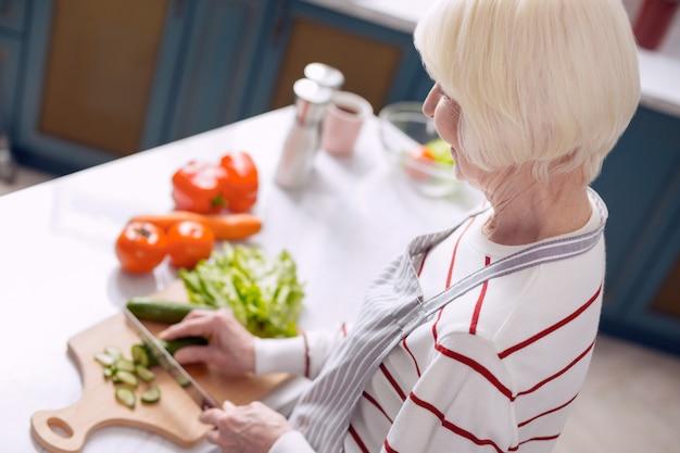 Beste kok. het bovenaanzicht van een prettige oudere vrouw die komkommers snijdt in de keuken en een salade maakt terwijl ze een schort draagt