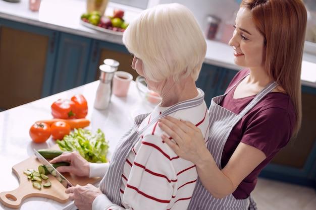 Beste kookduo. charmante jonge vrouw die zich hecht aan haar bejaarde moeder tijdens het koken van het diner in de keuken, de oudere vrouw die komkommers snijdt