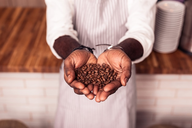 Beste kwaliteit. bovenaanzicht van mannelijke handen met koffiebonen van de beste kwaliteit die aan u worden getoond