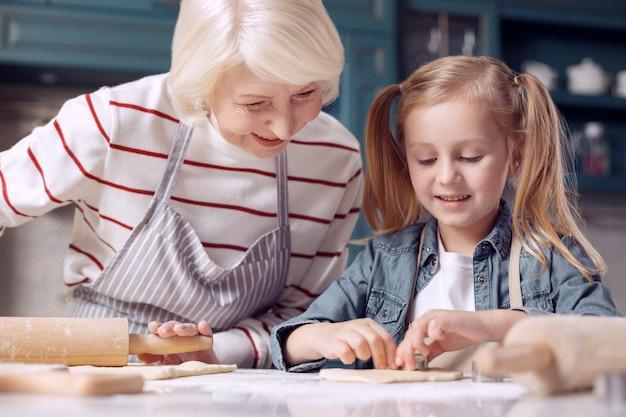 Beste leraar. aangename liefhebbende senior vrouw die kijkt naar haar geliefde kleine kleindochter die koekjes uitknipt terwijl ze het deeg uitrolt