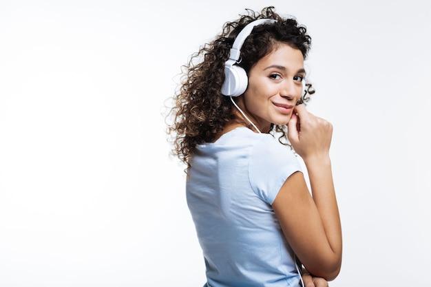 Beste muziek. aangename krullende jonge vrouw in een wit t-shirt, luisteren naar de muziek in koptelefoon op grijs