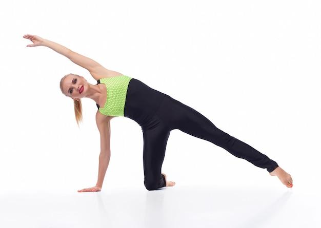 Beste ochtendtraining. sportieve jonge vrouw die geïsoleerd op wit traint en vrolijk glimlacht met een sexy sportoutfit geïsoleerd