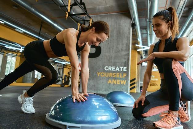 Beste oefeningen om fit te blijven jonge mooie vrouw in sportkleding die traint met personal trainer