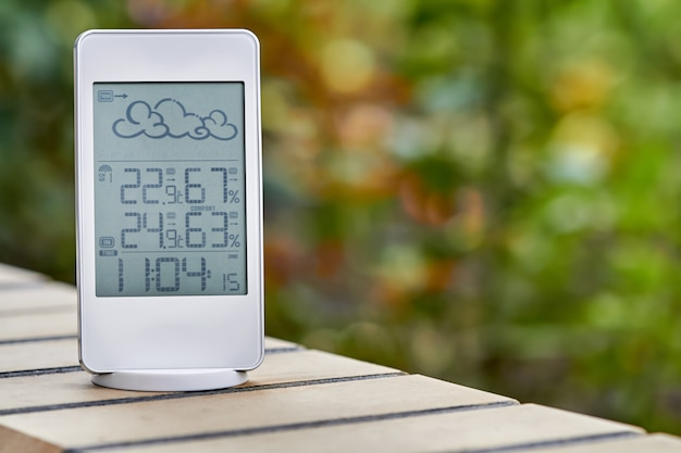 Beste persoonlijke weerstation apparaat met weersomstandigheden binnen en buiten op gebladerte achtergrond. home digitaal weersvoorspellingsconcept met temperatuur en vochtigheid.