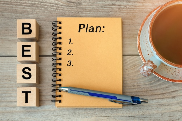 Beste plan - inscriptie op een notitieboekje en houten kubussen, een kopje koffie.