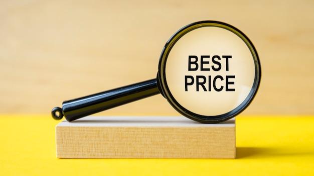 Beste prijs woord door vergrootglas op houten achtergrond. het vergrootglas is gemonteerd op een houten standaard op een gele tafel