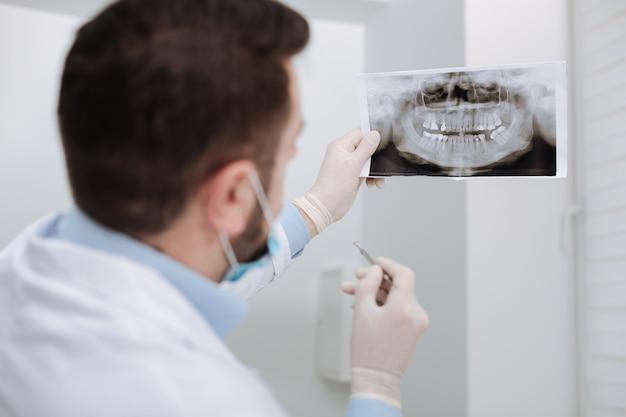 Beste privé-pediatrische arts die de scan van de tanden van de klant bekijkt en aan de diagnose werkt voordat hij met procedures begint