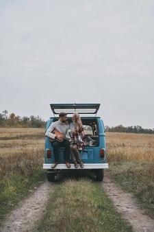 Beste reis. knappe jongeman gitaarspelen voor zijn mooie vriendin zittend in de kofferbak van blauwe retro-stijl minibusje