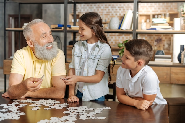 Beste samenwerking. glimlachende gelukkige hogere mens en zijn geliefde kleinkinderen die een puzzel doen en drie stukken van puzzel samen verenigen