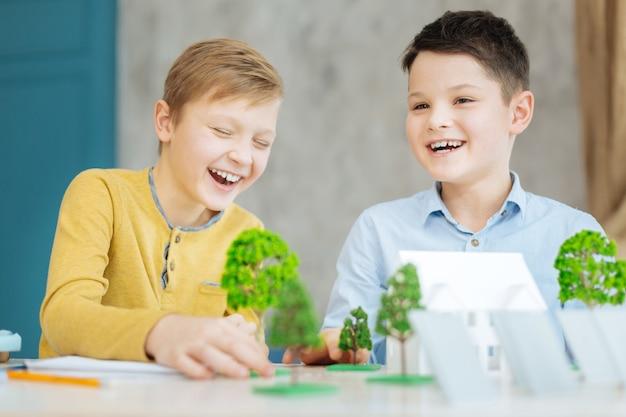 Beste samenwerking. vrolijke pre-tienerjongens zitten aan de tafel vol met modellen en lachen terwijl ze samen aan een ecologieproject werken