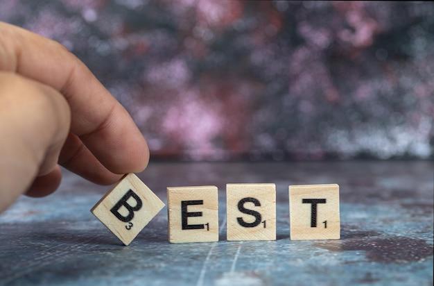 Beste schrijven met zwarte letters op houten dobbelstenen op blauwe achtergrond. hoge kwaliteit foto